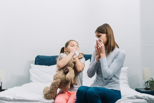Mother looking at her daughter blowing her nose with tissue paper Premium Photo