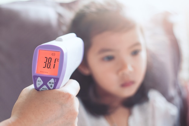 Mother measuring temperature her sick asian little child girl with infrared thermometer Premium Photo