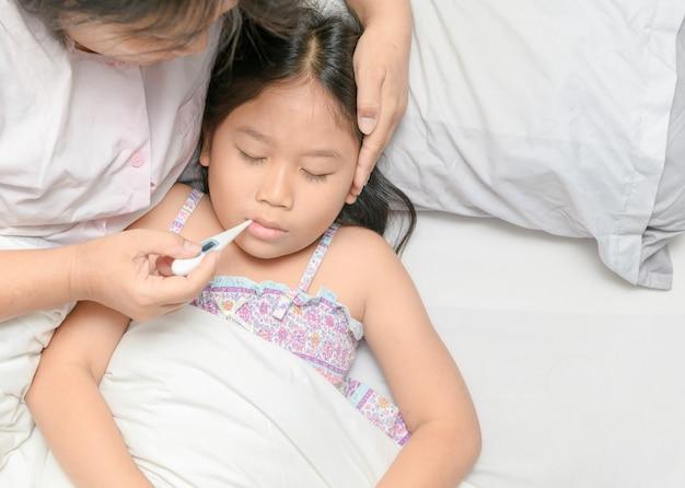 Mother measuring temperature of ill kid. Premium Photo