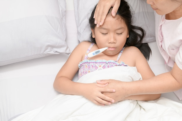 Mother measuring temperature of ill kid Premium Photo