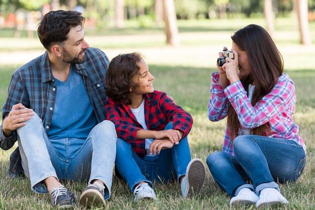 Madre che fotografa padre e figlio all'aperto nel parco Foto Gratuite