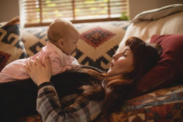 소파에 그녀의 아기와 함께 재생하는 어머니 무료 사진
