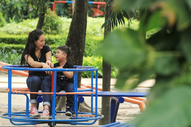A mother plays with her child cheerfully in the city park Premium Photo