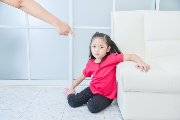 Mother pointing her finger to daughter while scolding her daughter at home Premium Photo