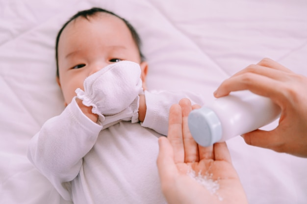 Mother preparing baby powder in her hand and 2 months old baby boy on bed. Premium Photo