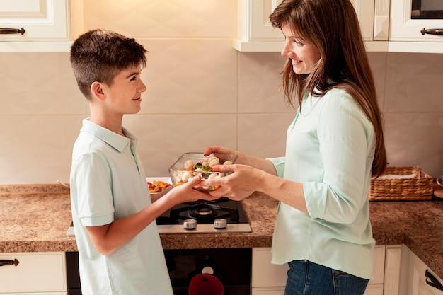 Мать готовит еду на кухне с сыном Бесплатные Фотографии
