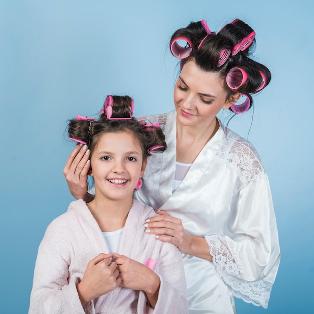 Mother putting curler in daughters hair Free Photo