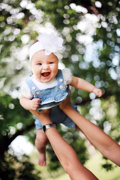 Mother raises up her smiling child. Premium Photo