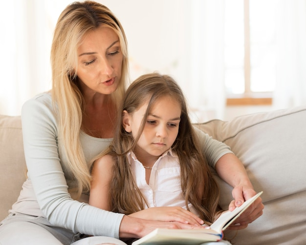 Мать, читая книгу дочери дома Бесплатные Фотографии