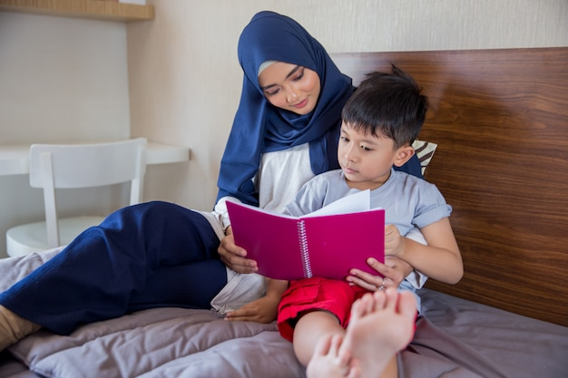 Mother reading a book with her boy Premium Photo