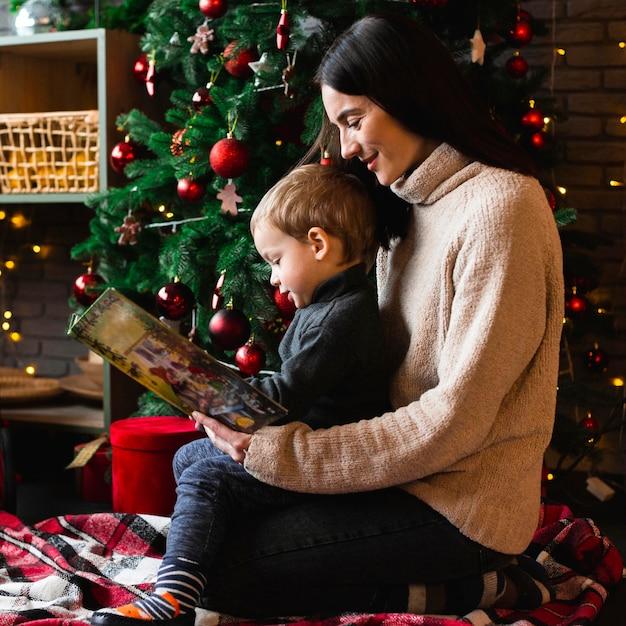 Мать читает рождественскую сказку своему ребенку Бесплатные Фотографии