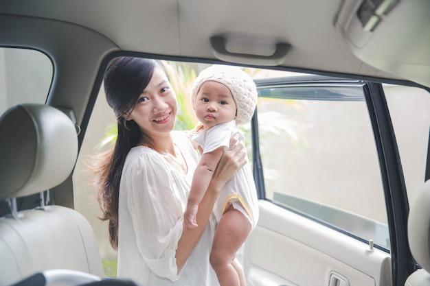 Мама готова посадить ребенка в автокресло Premium Фотографии