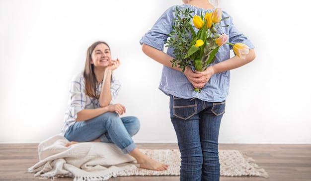 母の日、小さな娘が母親にチューリップの花束を贈ります。 無料写真