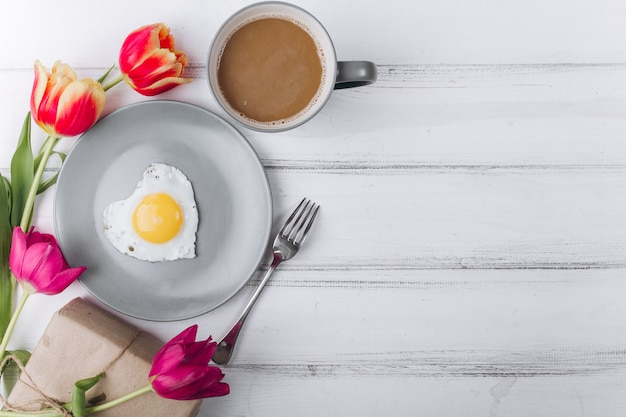 Mother's day composition. breakfast with tulips on white background. Premium Photo