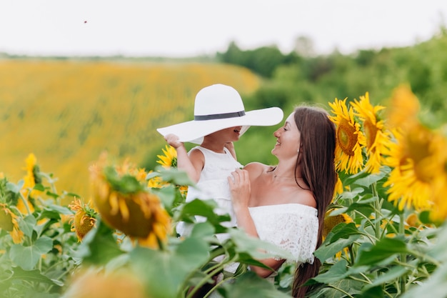 Mother's day. happy mother with the daughter in the field with sunflowers. mom and baby girl having fun outdoors. family concept. Premium Photo