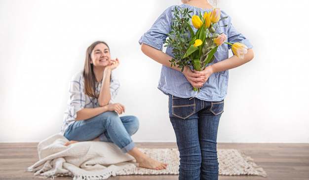 Mother's day, a little daughter gives her mother a bouquet of tulips. Free Photo