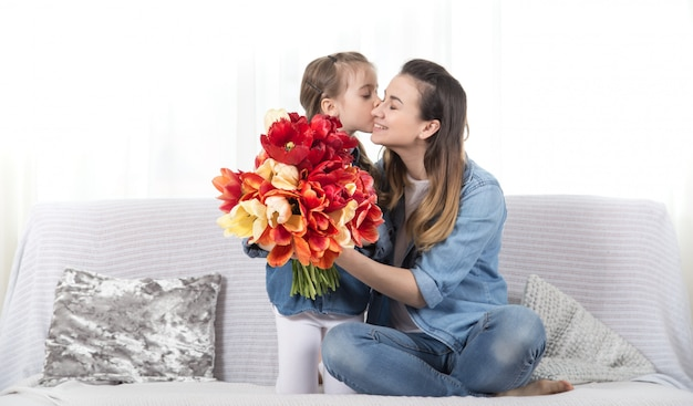 Mother's day. little daughter with flowers congratulates her mother Free Photo