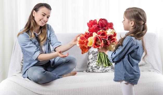 День матери. маленькая дочка с цветами поздравляет маму Бесплатные Фотографии