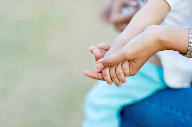 母親の愛によって捉えられた母親の手と赤ちゃんの写真コピースペースを持つ母親と子供のコンセプト Premium写真