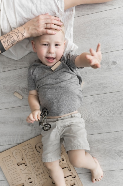 Mother's hand on little son's forehead lying on hardwood floor raising his hand Free Photo