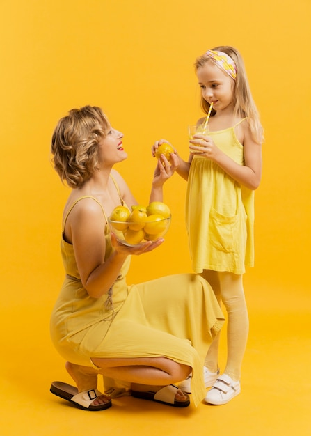 Mother showing her daughter lemons Free Photo