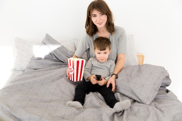 Mother and son eating popcorn Free Photo