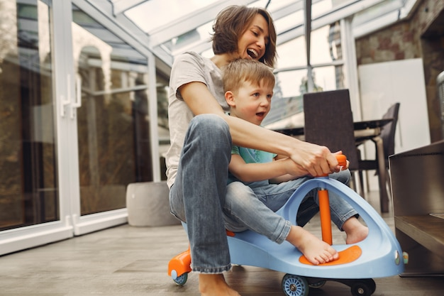Mother and son go around the apartment on a toy car Free Photo