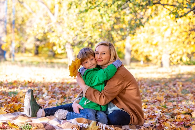 Mother and son hugging among autumn outdoor. concept of friendship between son and parents, family Premium Photo