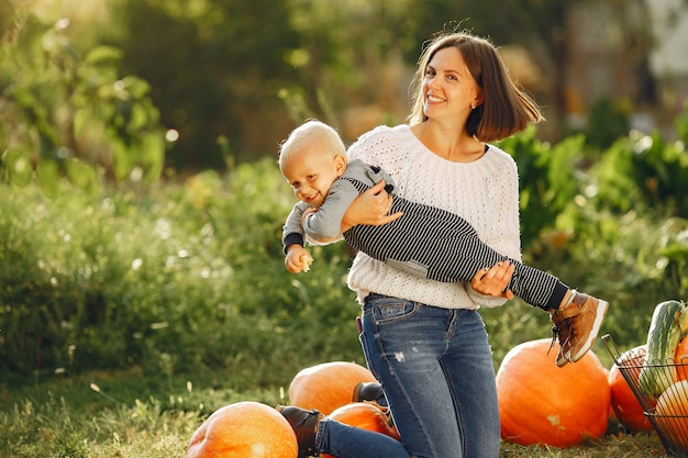 Mother and son sitting on a garden near many pumpkins Free Photo