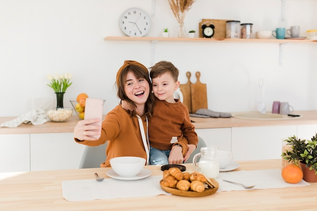 Mother and son taking selfies in the kitchen Free Photo