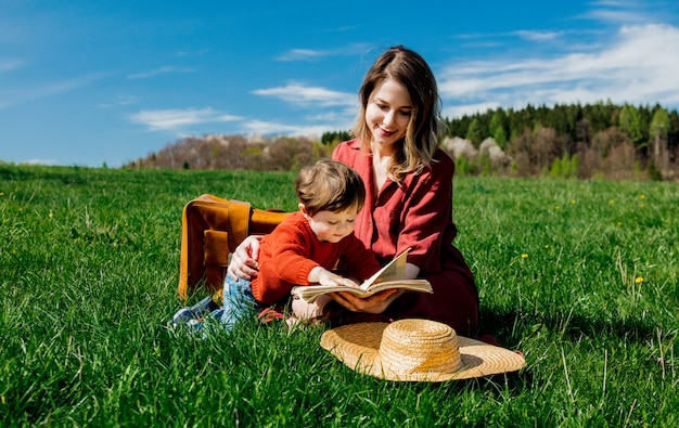 Mother and son with a book sitting on meadow. Premium Photo