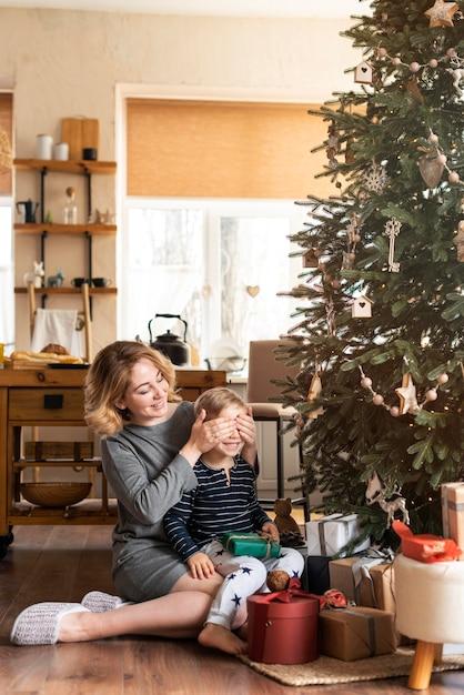 Мать удивляет мальчика с подарком рядом с елкой Бесплатные Фотографии