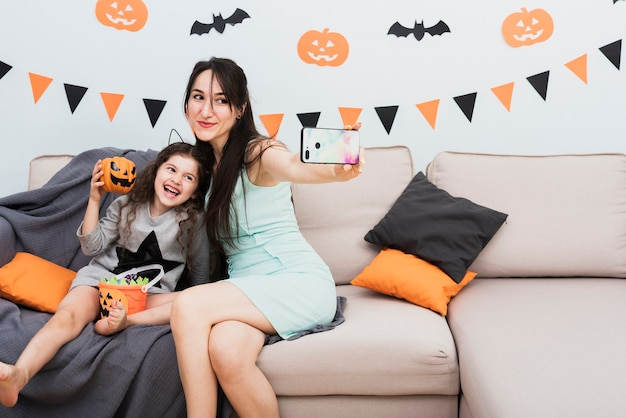 Mother taking a selfie with daughter on halloween Free Photo