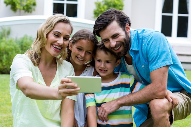 Mother taking selfie with family in yard Premium Photo