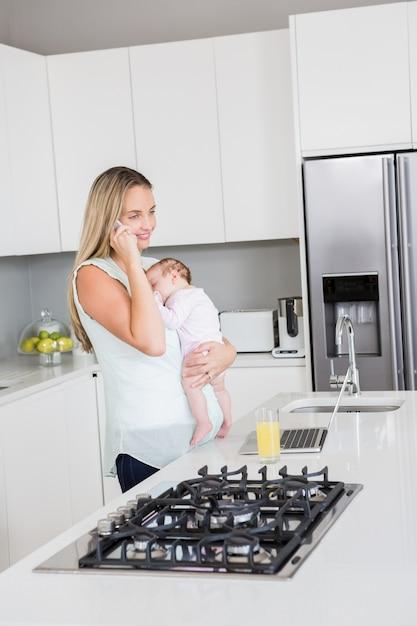 台所で赤ちゃんを運んでいる間携帯電話で話している母 Premium写真