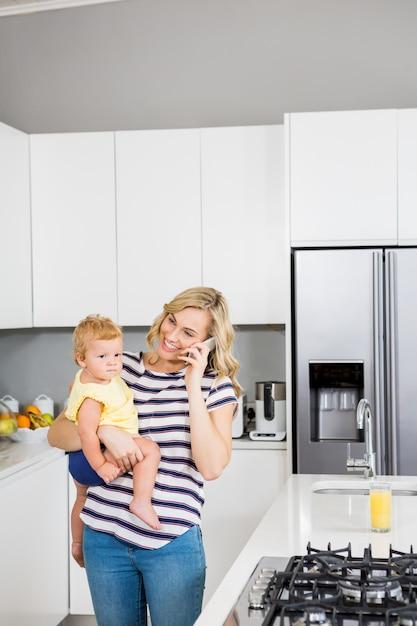 台所で彼女の女の赤ちゃんを保持しながら、母は携帯電話で話して 無料写真
