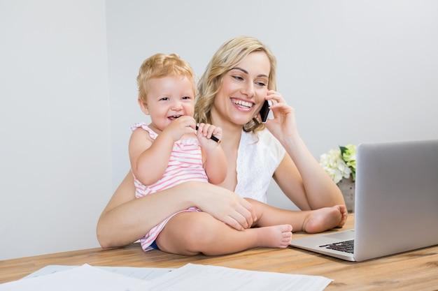彼女の女の赤ちゃんを保持しながら、母は携帯電話で話して 無料写真