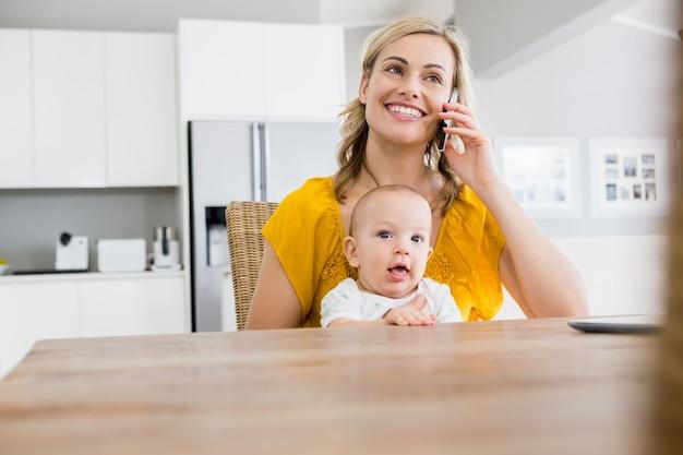 母は台所で赤ちゃんの男の子と携帯電話で話して 無料写真