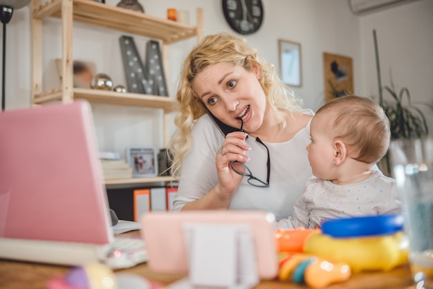 Mother talking on smart phone at home office Premium Photo