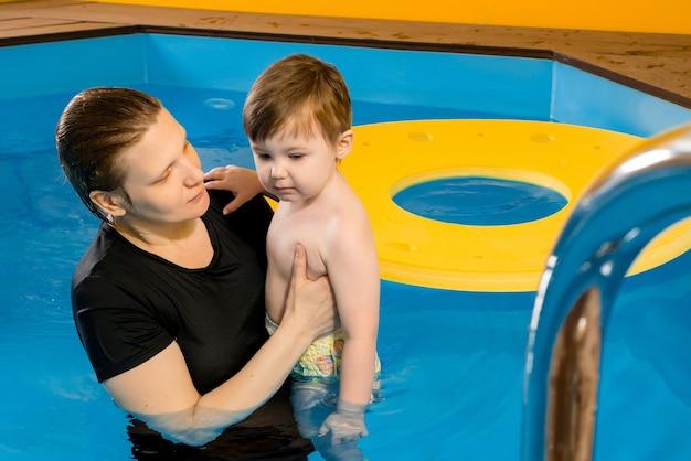 Мать учит ребенка плавать в закрытом бассейне Premium Фотографии