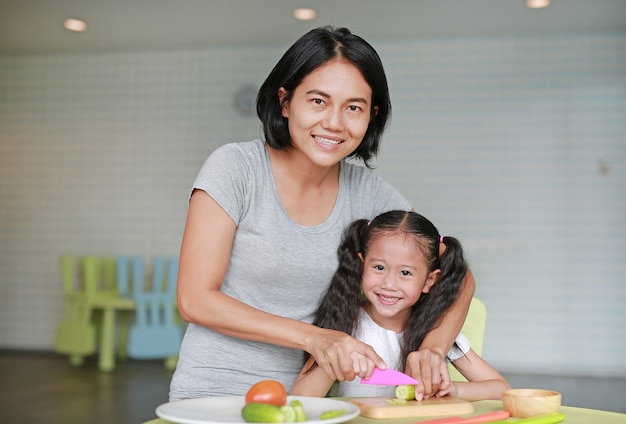 Mother teaches her children to cooking. close up asian mom and daughter slicing cucumber vegetable on chopping board at play room. Premium Photo