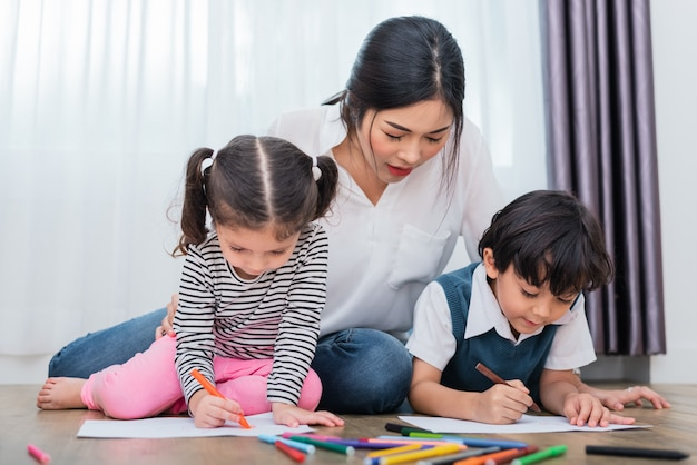 Mother teaching children in drawing class. daughter and son painting with crayon color in Premium Photo