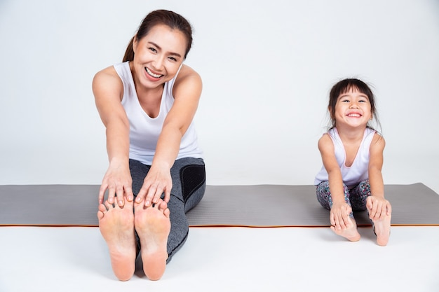 Mother teaching cute daughter to stretching leg muscles. Free Photo