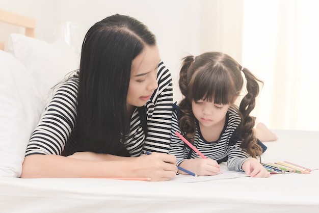 Mother teaching her daughter child to studying at home. Premium Photo