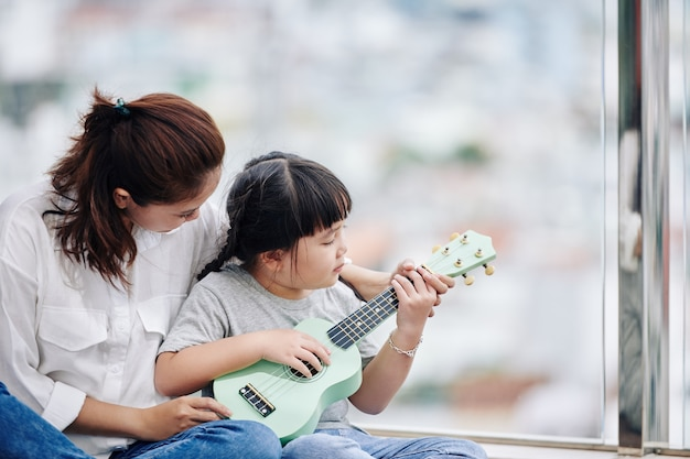 Mother teaching her little daughter how to play ukulele and showing her chords Premium Photo