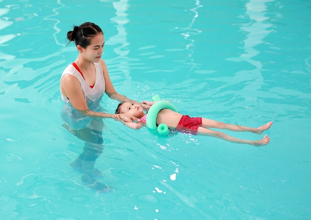 Mother teaching kid in swimming pool with foam noodle Premium Photo