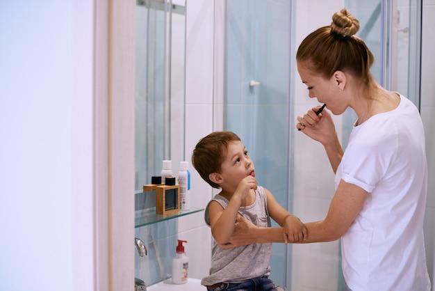 Mother teaching kid teeth brushing Premium Photo