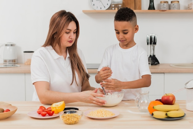 Mother teaching son to prepare food Free Photo