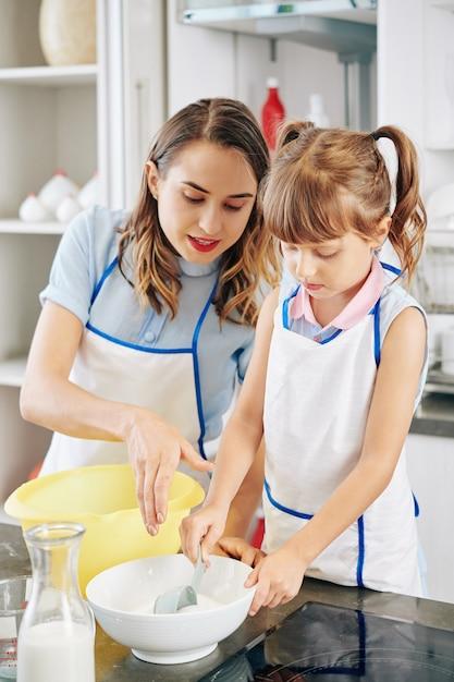 Мать говорит дочери, сколько сахара нужно добавить в миску, когда они делают тесто для торта Premium Фотографии