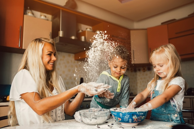 Mother throwing flour on her children Free Photo